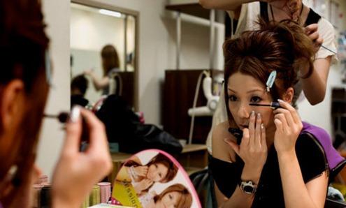图为:一个正在化妆的女子。在美肤这件事上,日本女孩绝对是世界女性中的前几名,日常生活中,很少看到日本女人上街披头散发、不化妆。